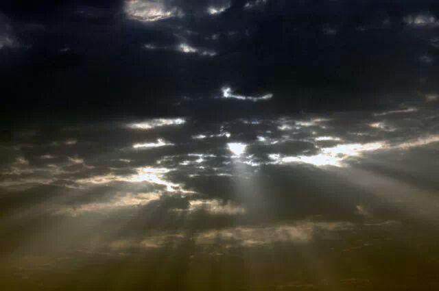 Entre las nubes sale el sol a su atardecer.